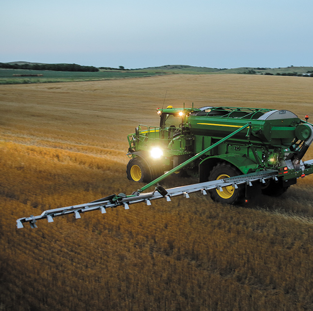 John Deere farmer in field spreading fertizilizer