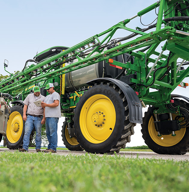 Farmers talking in front of John Deere sprayer