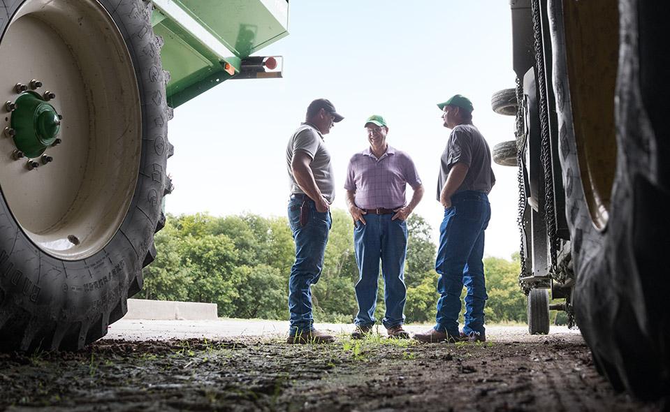 Farmers talking between machinery